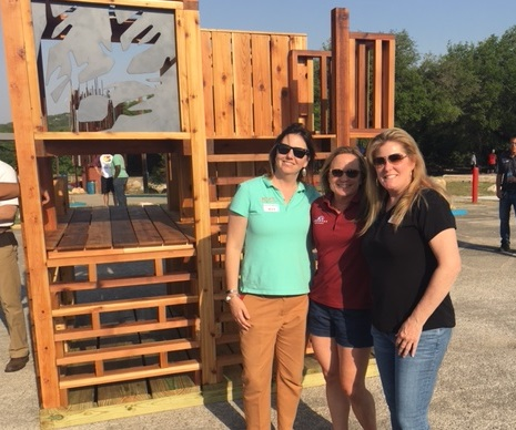 Three First Commercial Bank employees standing in front of a wooden children's playhouse.