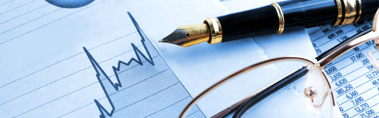 fountain pen and reading glasses laying on top of a financial chart
