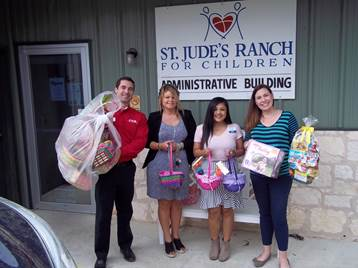 Four people with Easter baskets and donations